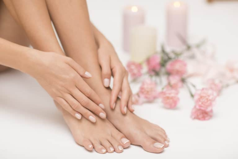 Dame mit sehr schönen füßen und händen, im Hintergrund sieht man weiße Kerzen und Rosen.