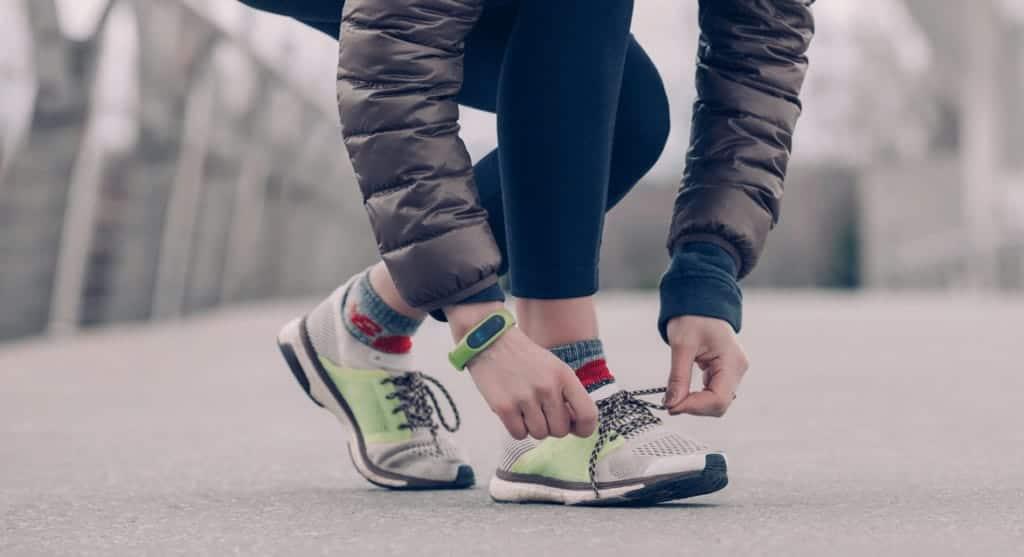 Sportler bindet sich die Laufschuhe zu.