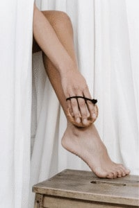 Bild von einem nackten Bein und Fuß mit einer Hand die das Bein mit einer Bürste bürstet.