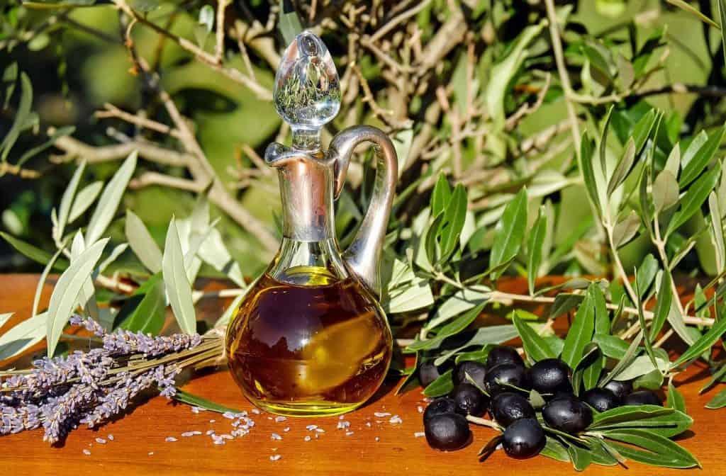 Olivenöl in einer Karaffe draußen auf einem Tisch mit Oliven und Ästen.