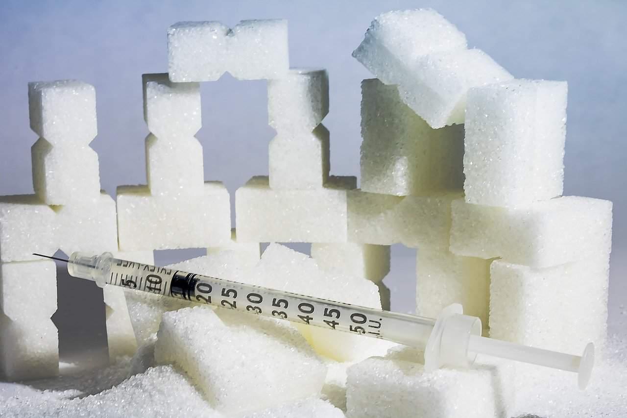 Zuckerwürfel und Spritze, sinnbildlich für Diabetes.