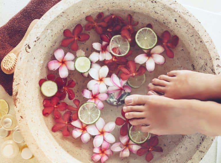 Frau nimmt ein Fußbad mit Blüten und Limetten und Zitronen