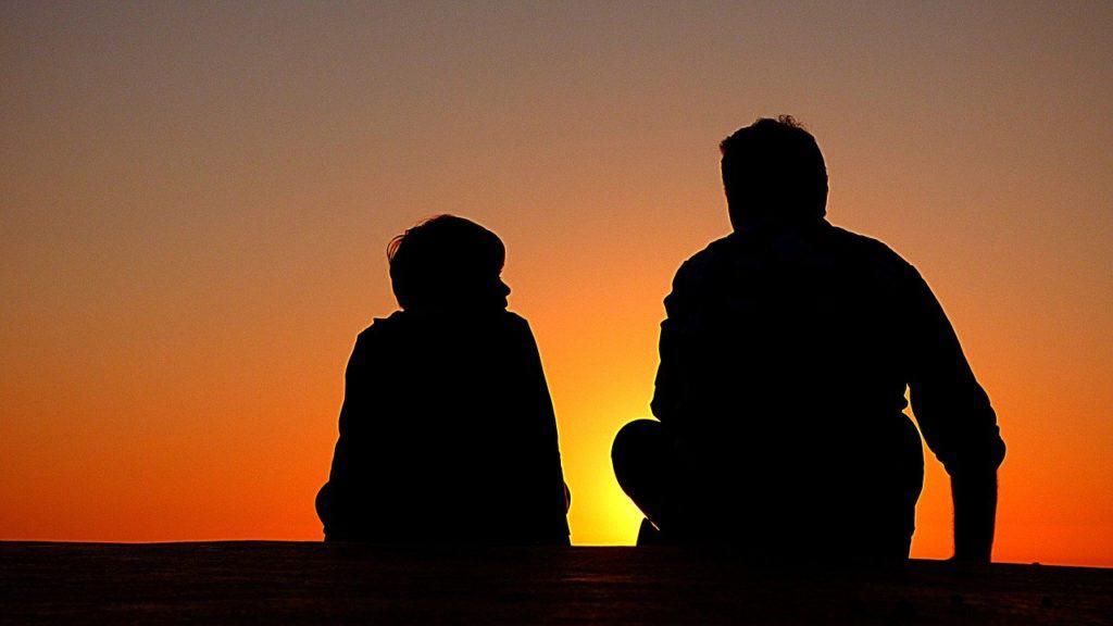 Ein Mann sitzt mit einem Kind im Sonnenuntergang und bespricht etwas.