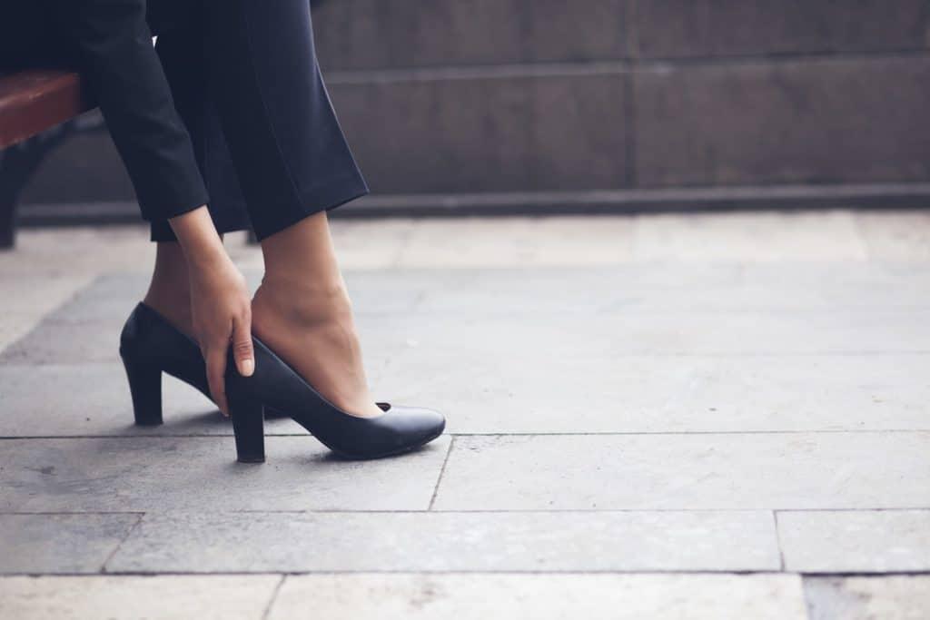 Frau langt sich an drückenden Schuh