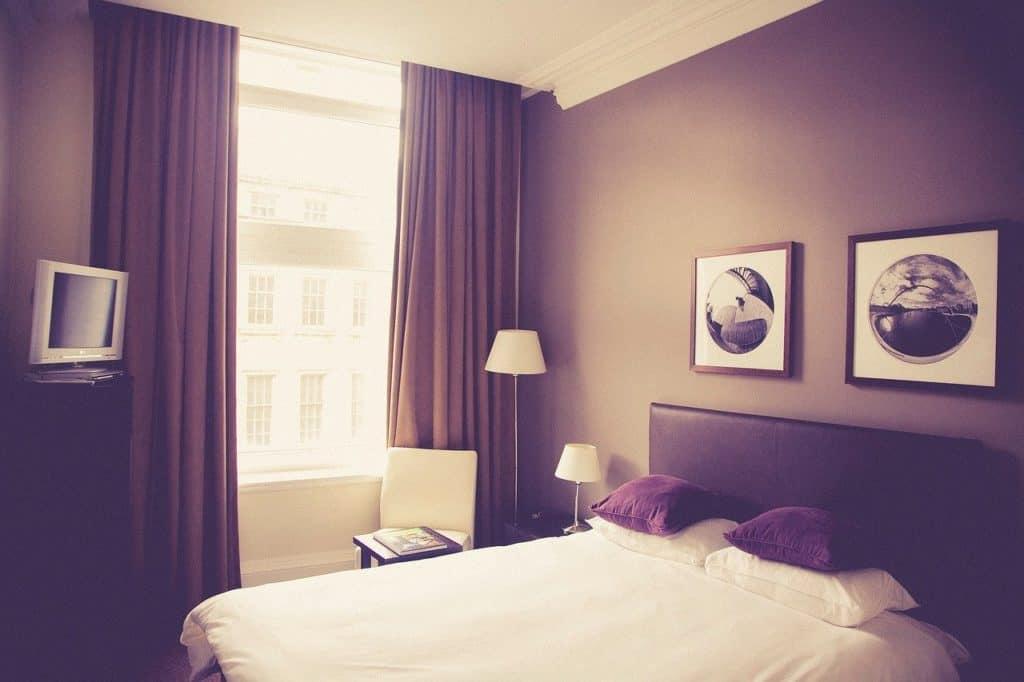 Hotelzimmer, in dem ein Bett, zwei Bilder, eine Lampe und ein kleiner Fernseher zu sehen sind.
