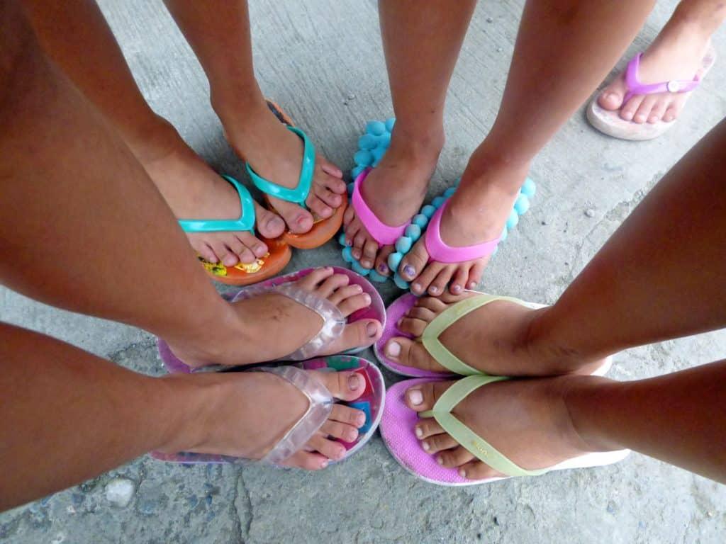 Nagelpilz Kind: Vier Kinder in Flip Flops, bei denen nur die Beine zu sehen sind.