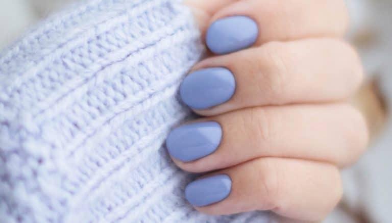 Weiche Fingernägel der Hände mit blauem Nagellack bei einer Frau