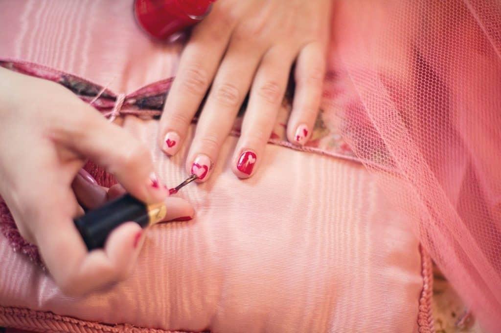 Frau lackiert sich die Finger.
