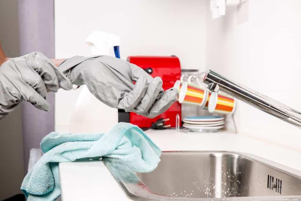 Frau mit Putzhandschuhen über Waschbecken. Die Handschuhe helfen gegen weiche Fingernägel