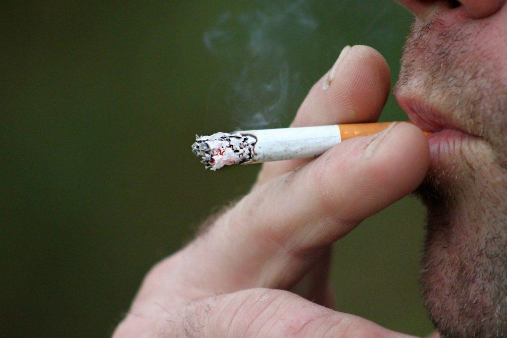 Mann hält Zigarette zwischen zwei Fingern und raucht.