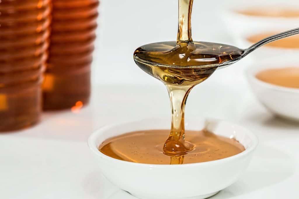 Honig, der über einen Löffel in eine Schale fließt