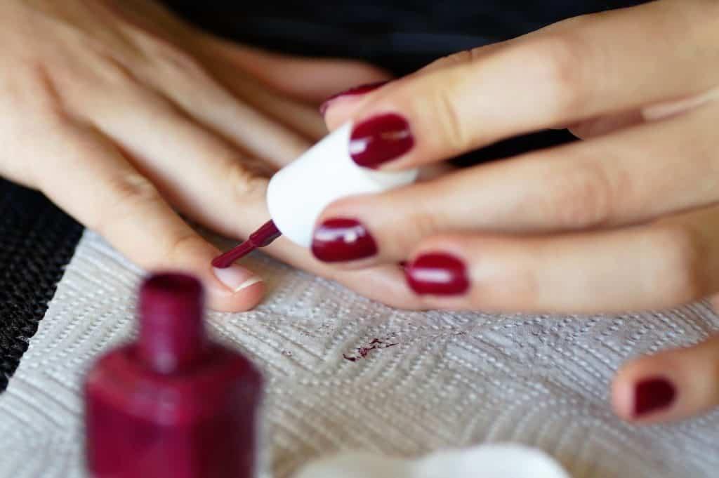 Maniküre, eine Frau lackiert sich die Nägel rot