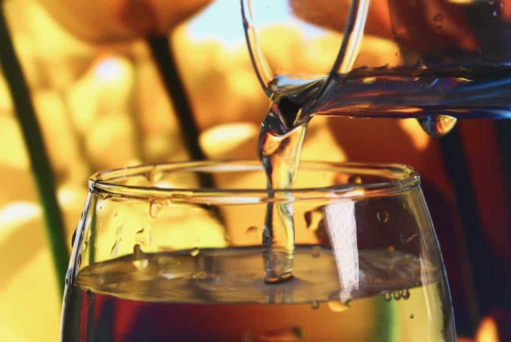 Wasserglas, was mit Wasser aus einer Karaffe befüllt wird.