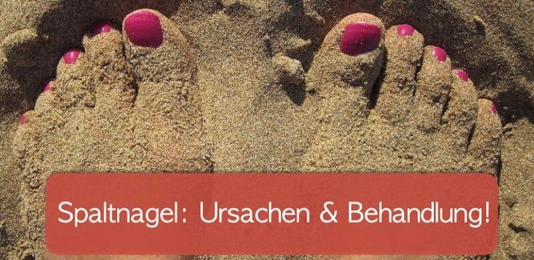Beide Füße einer Dame im Sand.