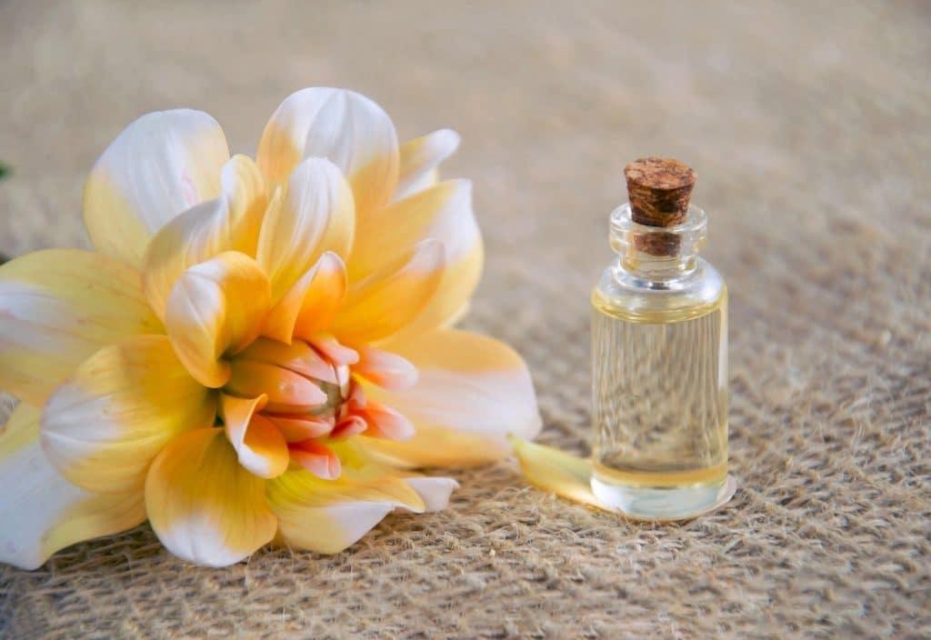 Kosmetiköl in Glasfläschchen mit Korkstopfen und Blüte nebenan. Symbol für Hausmittel gegen Warzen