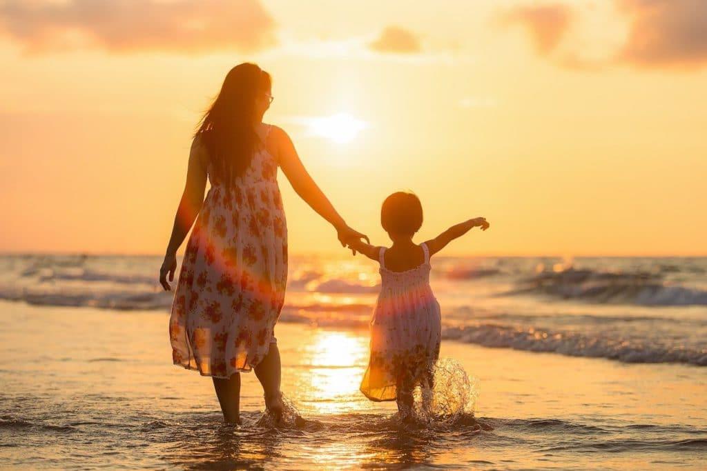 Mutter und Tochter von hinten fotografiert, spazieren am Strand im Wasser entlang