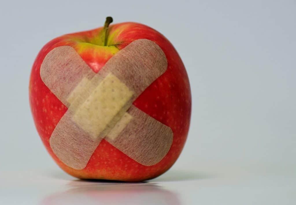 Roter Apfel mit Pflaster, Symbolisch für Warzen Pflaster