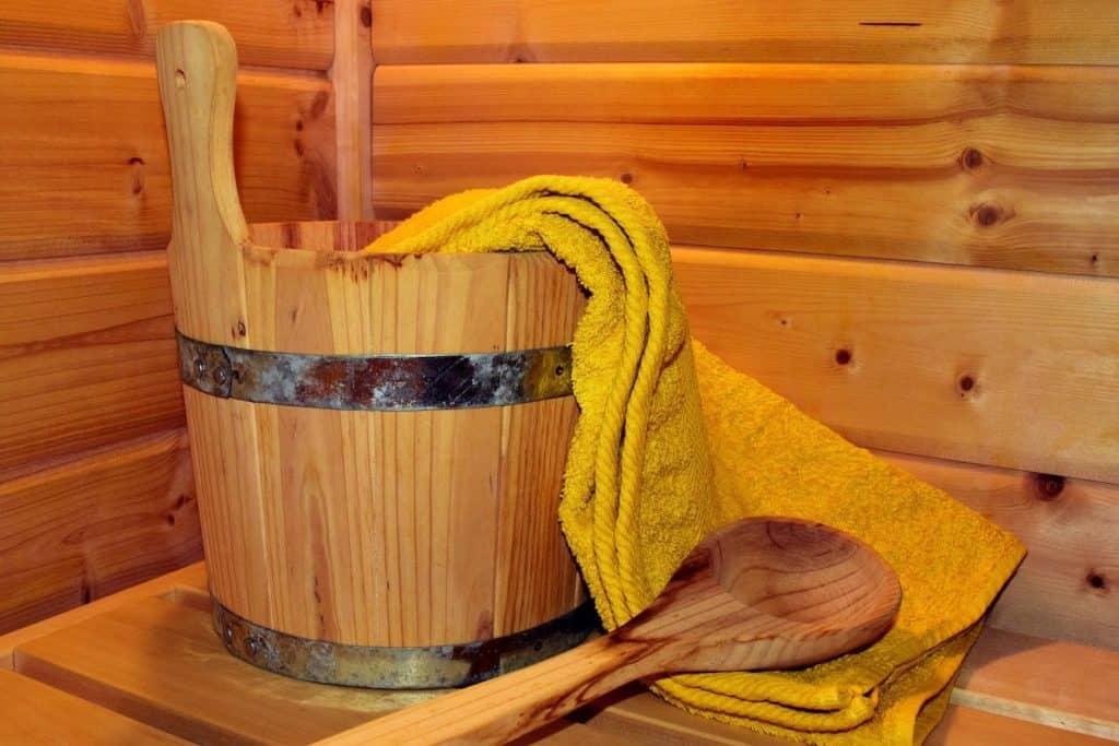 Sauna mit Handtuch und Eimer mit Löffel für den Aufguss.