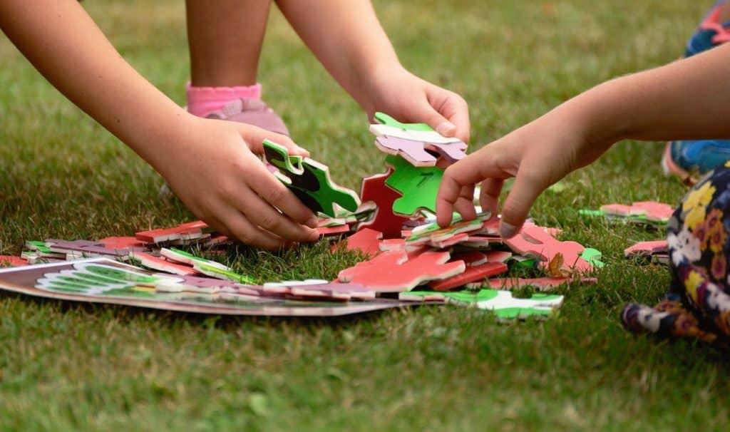 Kinderhände die ein Puzzle zusammensetzen.