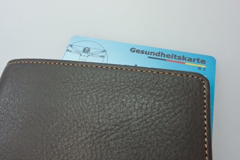 Medizinische Fußpflege Nagelpilz Kosten: zahlt Krankenkasse? Gesundheitskarte in Geldbeutel.
