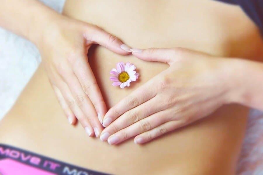 Hände einer Frau formen ein Herz um ihren Bauchnabel. Direkt auf dem Bauchnabel liegt eine Blüte.