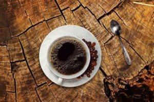 Kaffeetasse auf einem Holztisch von oben fotografiert.