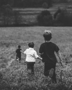 Kinder spielen in einer Wiese fangen