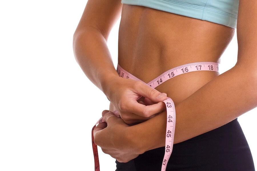 Frau mit Maßband um den Bauch als Zeichen zur Gewichts Abnahme