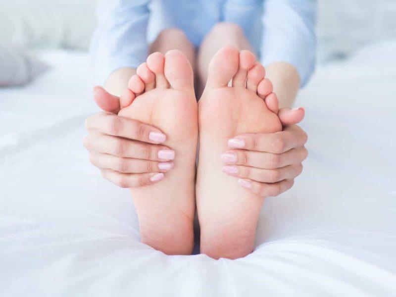 Zwei Füße einer Frau, sitzend auf dem Bett. Die Füße sind besonders gefährdet an einer Pilzinfektion (v.a. Fusspilz) zu erkranken.